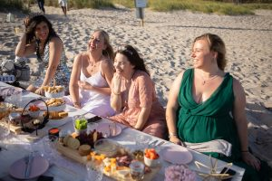 Photo of women having a glamorous picnic at the beach as part of a retreat.